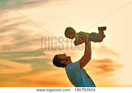 Happy father playing with son on sunset background .The concept of father's day