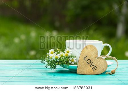 A cup of fragrant hot tea with herbs and a wooden heart. A useful hot drink with chamomile flowers. Natural medicine. Copy space