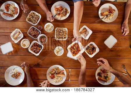 Friends at a table sharing Chinese take-away, overhead view