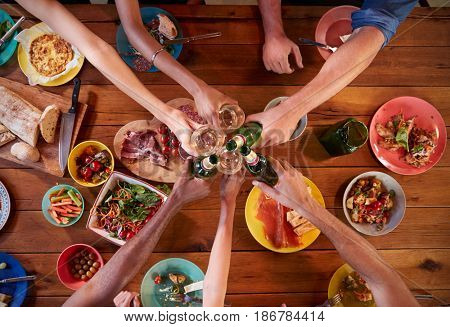 Friends making a toast at a dinner table, overhead, close up