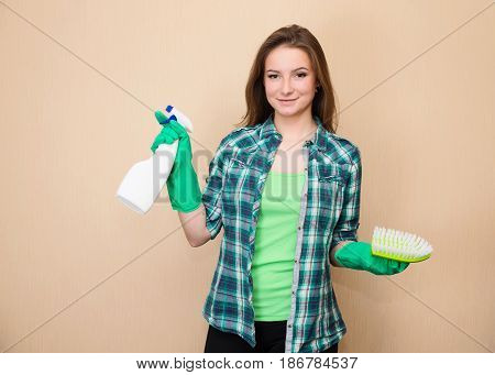 Spring cleaning. Cleaning woman with cleaning spray bottle and brush happy and smiling. Beautiful cleaning girl or housewife. Mixed race woman.