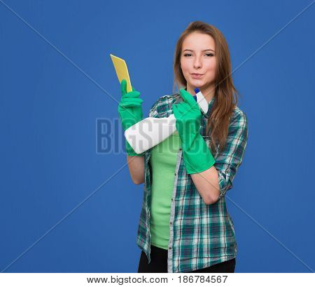Cleaning woman with cleaning spray bottle happy and smiling. Beautiful cleaning girl isolated on blue background with copyspace. Mixed race woman.