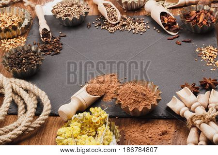 Different spices in bakeware with wooden scoops on the slate slone background soft focus background