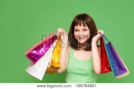 Close-up portrait of happy young girl with colorful shopping bags isolated on green background. Sales. Shopper.