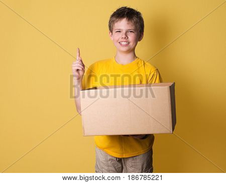 Smiling boy with a box on yellow background. Think out of the box concept.