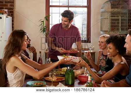 Host and friends pass food round the table at a dinner party