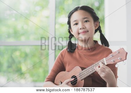 Beautiful Asian girl playing ukulele at her room