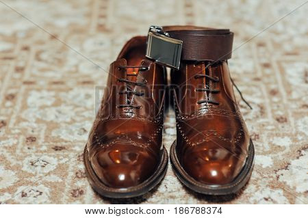 A new pair of tan leather shoes and belt on beige carpet
