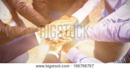 High angle view of well dressed businesspeople stacking hands in office