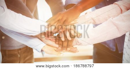 Mid section of business team stacking hands in office