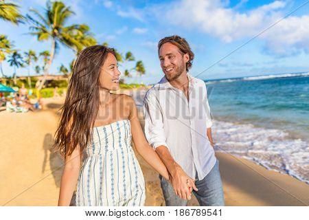 Beach couple happy holding hands on hawaiian holidays in Waiohai beach, Poipu in Kauai, Hawaii, USA. Newlyweds people in love on honeymoon. Asian woman, Caucasian man.