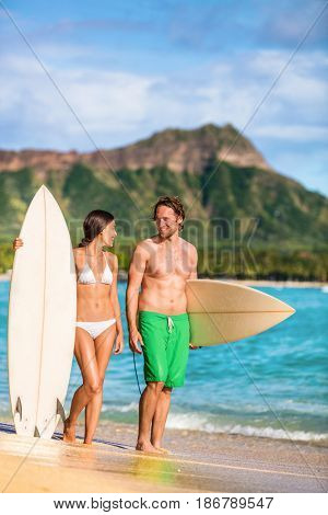 Beach couple surfing in Hawaii relaxing at sunset standing with surfboards on waikiki beach, Honolulu, Oahu, USA. Summer holidays travel landscape. Happy people having fun.