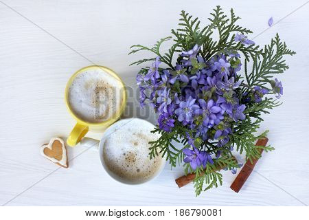 pair of cups of foamy coffee with biscuits cinnamon and a bouquet of flowers top view/ Breakfast for lovers in spring colors