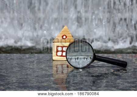 magnifying glass and the layout of the wooden house on a background of a waterfall / careful choice of location for the construction of