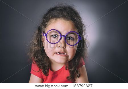 Portrait of a funny six years girl with glasses making faces. Black background. Studio shot