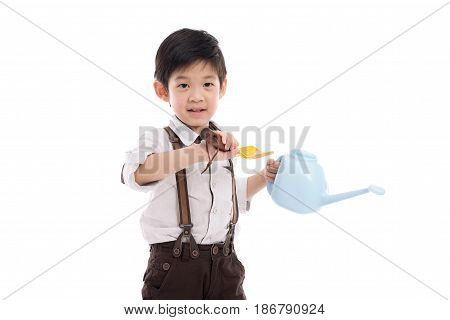 Cute Asian child holding gardening tools on white background isolated