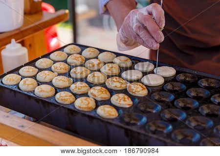 Man cooking little pancakes on the frypan