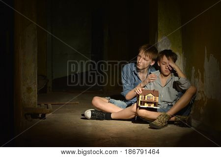 Little boys in a dark cellar with toy house
