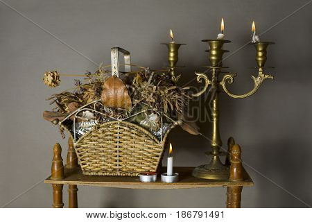 Bronze candle holder swith burning candles and vintage objects on a retro wooden shelf