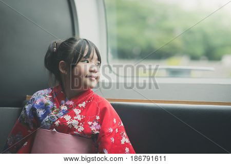 Little asian girl wearing red kimono looking through window. She travels on a trainvintage filter