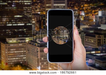 Hand holding mobile phone against white background against illuminated building in city at night