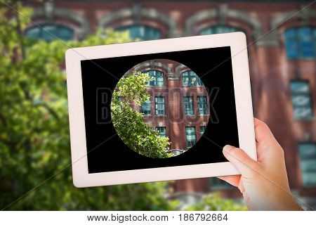 Masculine hand holding tablet against tree against building