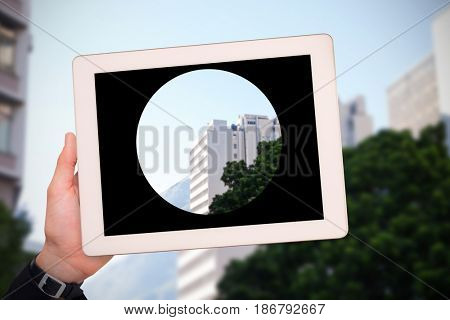 Masculine hand holding tablet against low angle view of city buildings