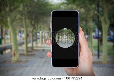 Hand holding mobile phone against white background against footpath amisdt treelined