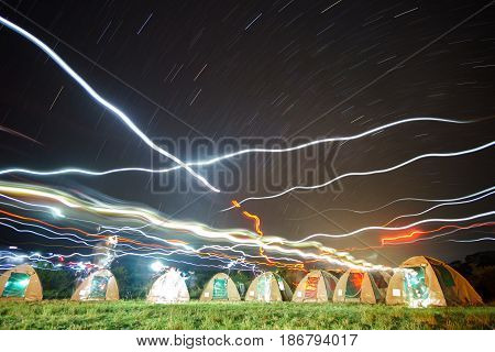 Night view of tents in african park with star trails and headlamp lights during sleeping time