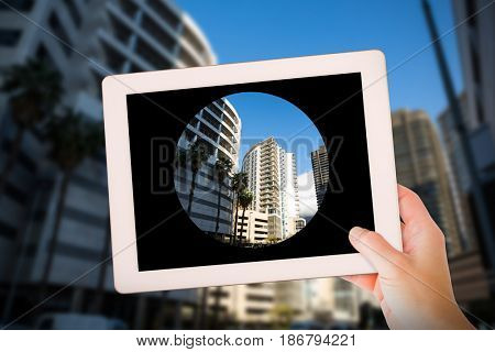 Masculine hand holding tablet against buildings in city