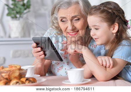 Grandmother with granddaughter playing in a tablet computer