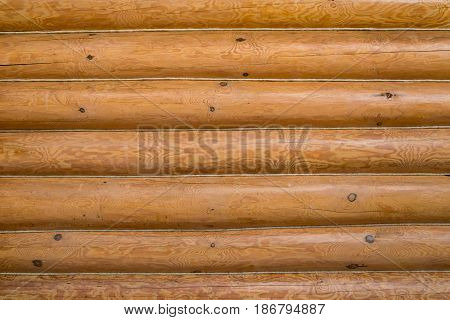 Wooden wall of a log house. Log Cabin Or Barn Unpainted Debarked Wall Textured Horizontal Background With Copy Space.