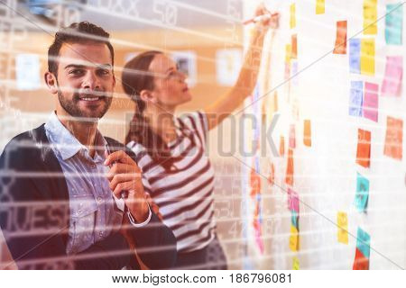 Stocks and shares against portrait of businessman with female colleague by whiteboard