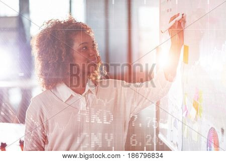 Stocks and shares against businesswoman writing on whiteboard