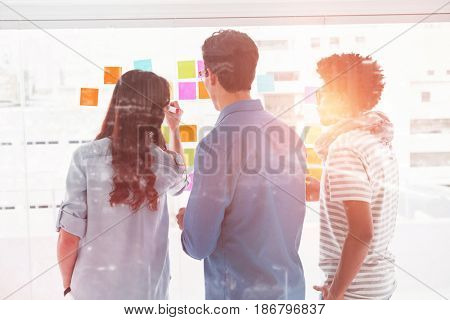 High angle view of illuminated cityscape against young creative businessteam discussing over adhesive notes
