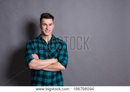 Young casual man model studio portrait. Boy style, trendy hipster in checkered shirt look with cool hairstyle