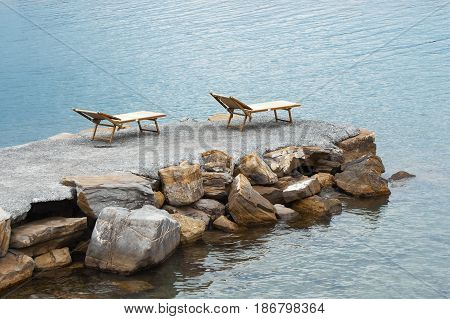 Two wooden chaise lounges on an artificial stone pier.