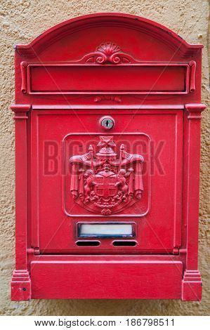 The old classic mailbox is red on the plastered wall of the old house.