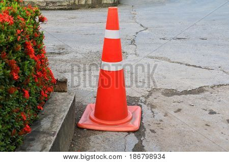 Traffic cone white and orange stripes on gray asphalt with copy space