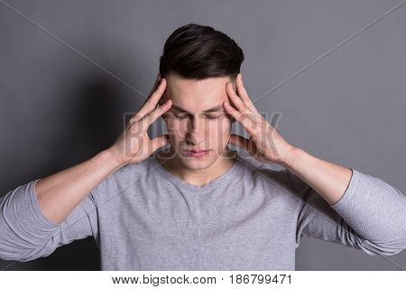Concentration. Young man consider something, touch his head at gray studio background. Thinking, solving problems