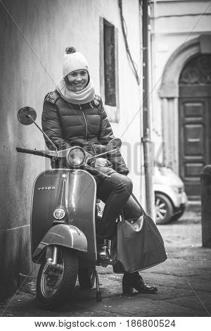 VITERBO, ITALY. January 22, 2017: A beautiful smiling woman sitting on an old Italian motorcycle at Viterbo in Italy. Black and white.