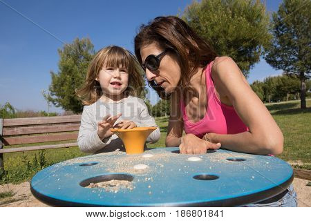 Child And Mother Playing With Sand At Playground