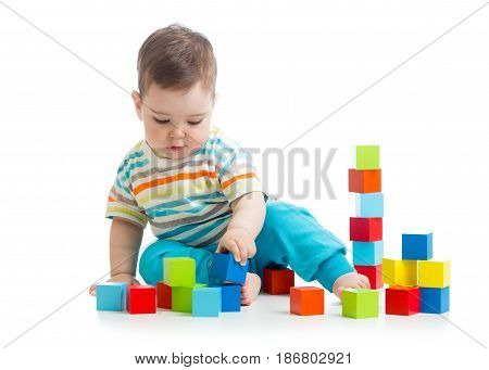 Lovely toddler baby playing with building cubes. Isolated on white background.