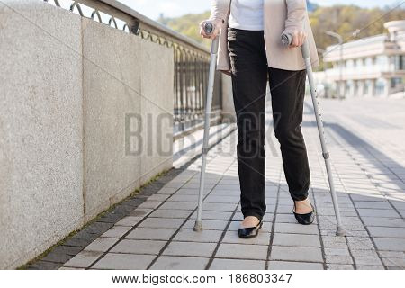 Not fun getting on. Moody shy thoughtful lady using crutches and concentrating while walking outdoors