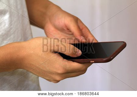 Focus on young man hand holding a mobile phone / smartphone, can be watching a video or typing a message