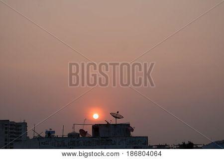 sun go down kite fly in red sky block of building in silhouette