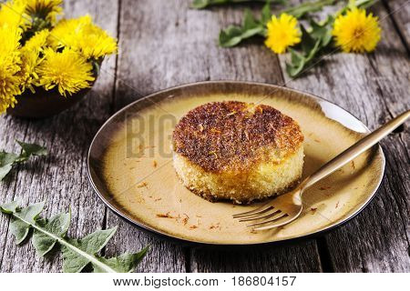 Pieces of simple homemade semolina sponge cake with saffron on vintage wooden table decorated dandelions. Selective focus
