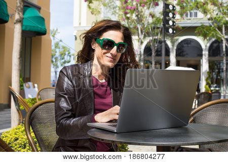 Woman In Bar Oudoors Typing In Laptop
