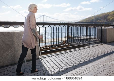 Everything can be. Gentle sad confusing woman walking on the quay while expressing amaze and looking at the accidental occurrence
