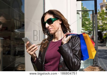 Woman Next To Store Showcase Using Mobile Phone